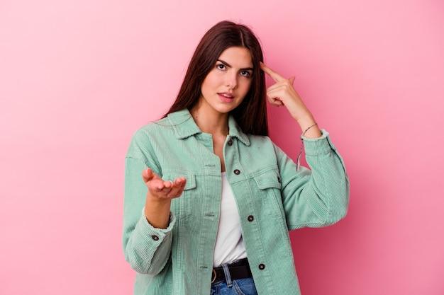 핑크 잡고 손에 제품을 보여주는 젊은 백인 여자.