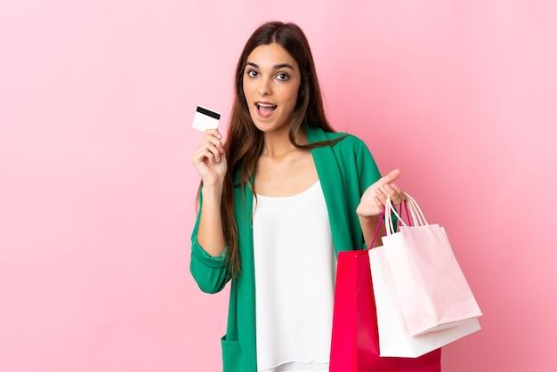 쇼핑백과 신용 카드를 들고 분홍색에 젊은 백인 여자