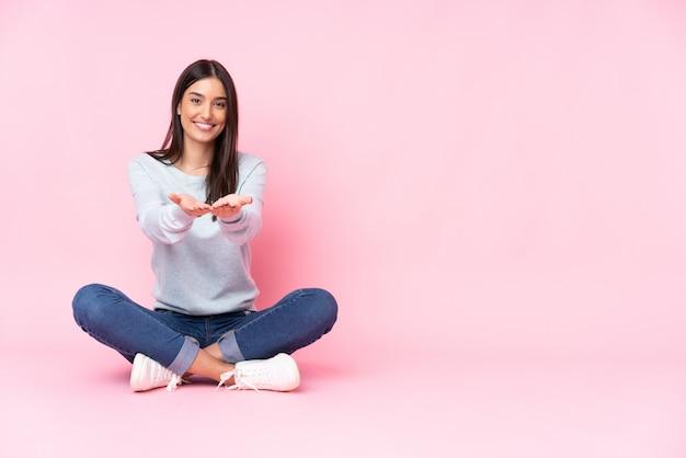 Молодая кавказская женщина на розовой стене держа пустое пространство на ладони