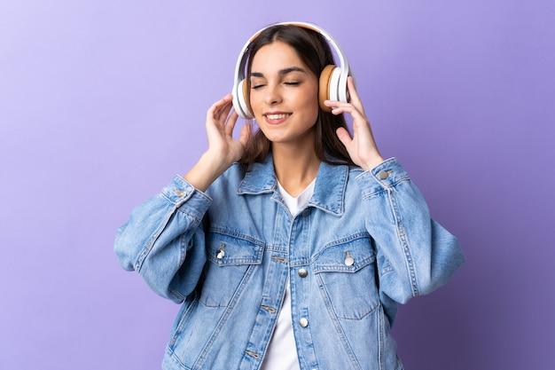 Молодая кавказская женщина на фиолетовом прослушивании музыки и пении