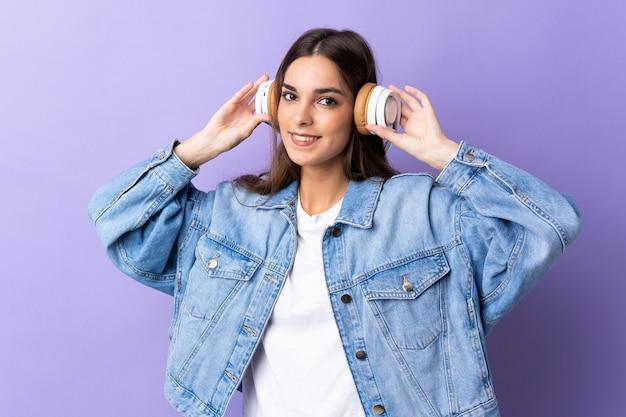 Молодая кавказская женщина на фиолетовом прослушивании музыки