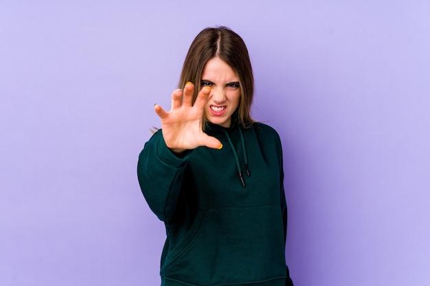 猫を模倣した爪、攻撃的なジェスチャーを示す紫色の若い白人女性。