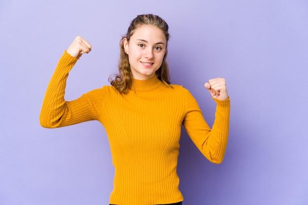 Молодая кавказская женщина на фиолетовом показывает жест силы руками, символ женской силы