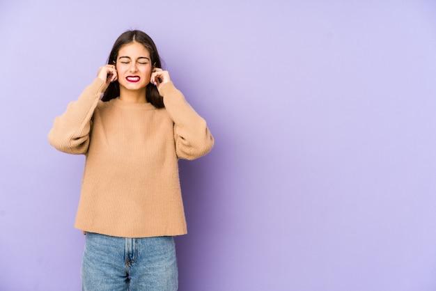Молодая кавказская женщина на фиолетовой стене покрывая уши с пальцами, усиленными и отчаянными громко окружающими.