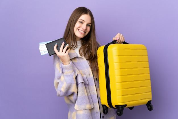 スーツケースとパスポートとの休暇で紫色の壁に若い白人女性
