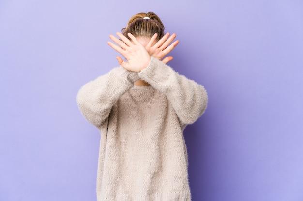 紫色の壁に2本の腕を組んでいる若い白人女性、否定の概念。