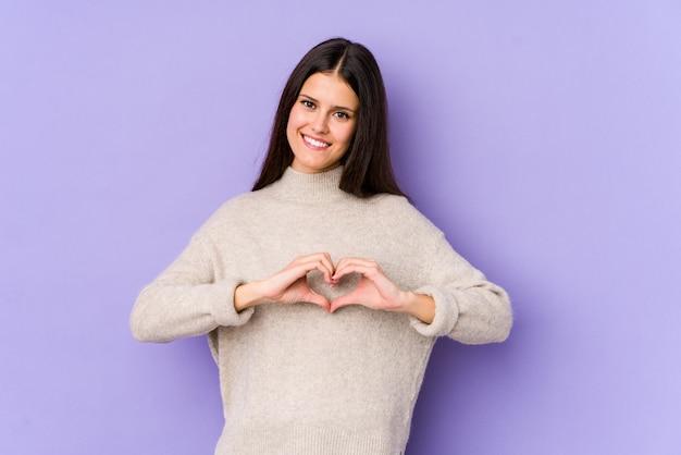 Молодая кавказская женщина на фиолетовой стене усмехаясь и показывая форму сердца с руками.
