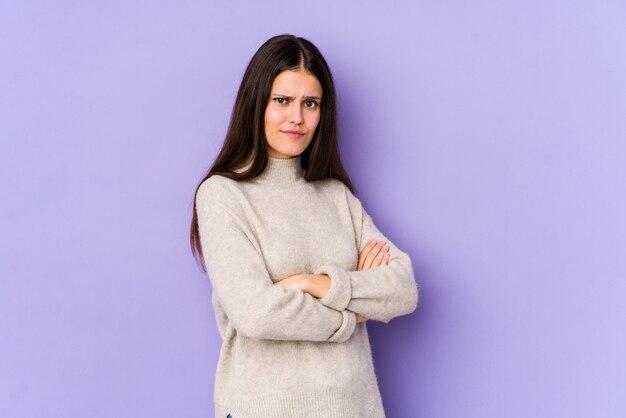 紫色の壁に不審な、不確かな若い白人女性があなたを調べます。