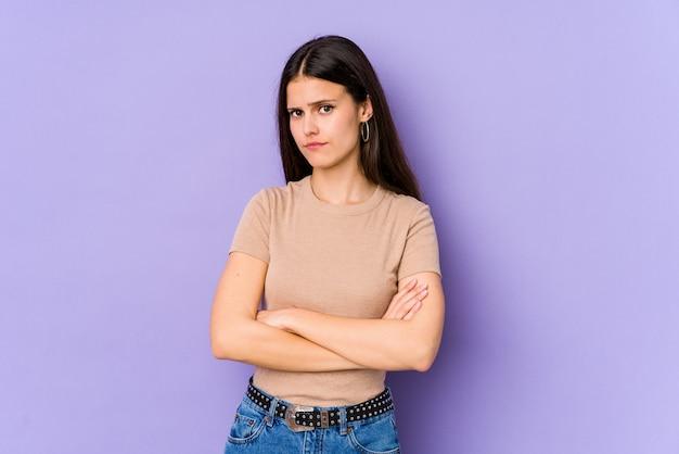 皮肉な表現に不満のある紫色の壁に若い白人女性。