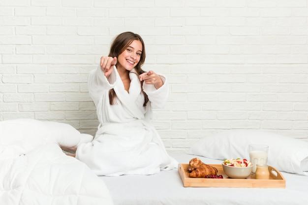 ベッドの上の若い白人女性は正面を指している陽気な笑顔。