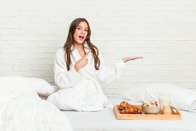 ベッドの上の若い白人女性は、手のひらにコピースペースを持って興奮しました。
