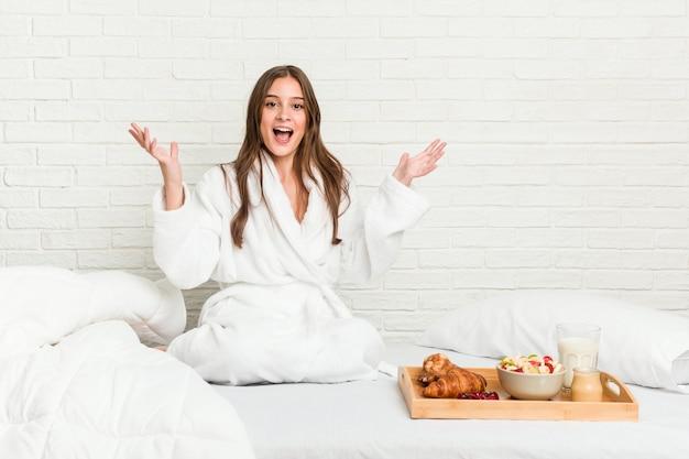 ベッドの上の若い白人女性は、嬉しい驚きを受け取り、興奮し、手を上げます。