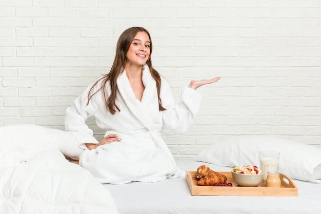 手のひらにコピースペースを示し、腰に別の手を保持しているベッドの上の若い白人女性。