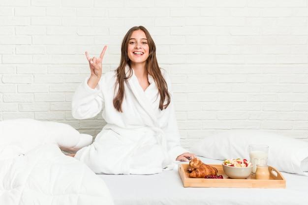 革命の概念として角のジェスチャーを示すベッドの上の若い白人女性。