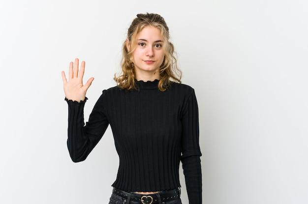 指で5番を示す陽気な笑顔の白い背景の若い白人女性。