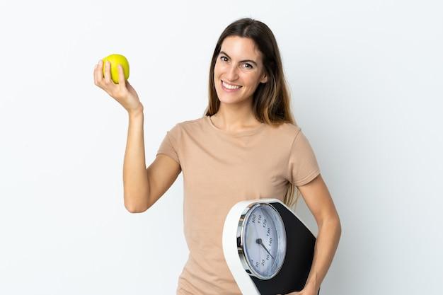 Молодая кавказская женщина на белой стене с весами и с яблоком