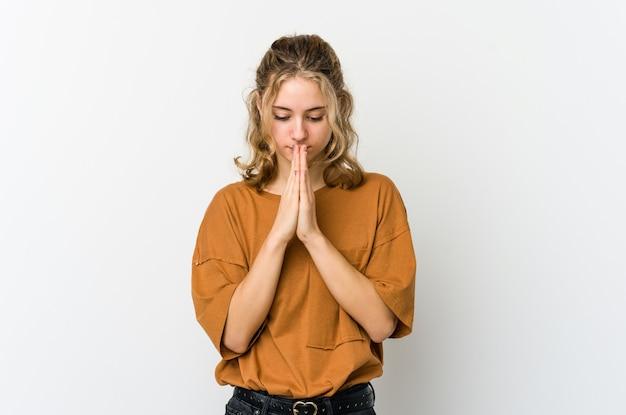 祈り、神のインスピレーションを探している宗教的な人を示す白いwallprayingの若い白人女性。