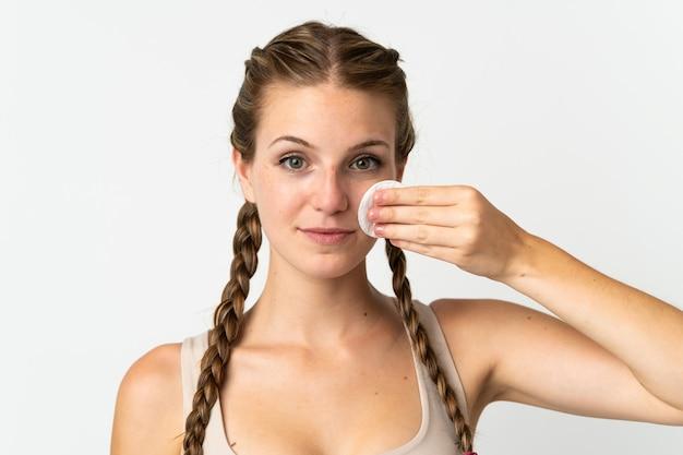 彼女の顔から化粧を取り除くためのコットンパッドと白の若い白人女性