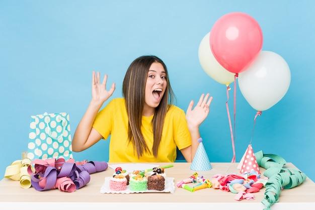 勝利または成功を祝う誕生日を組織する若い白人女性、彼は驚いてショックを受けています。