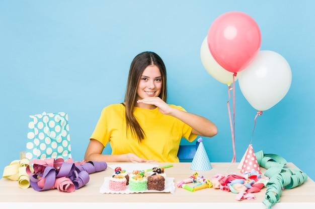 Молодая кавказская женщина организует день рождения, держа что-то обеими руками, презентация продукта.