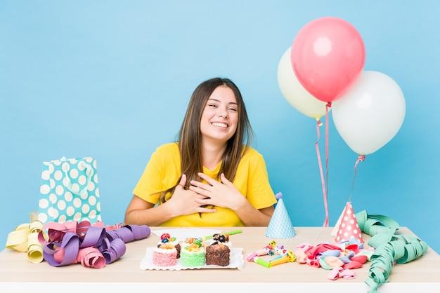 생일을 조직하는 젊은 백인 여자는 행복하게 웃고 뱃속에 손을 유지하는 재미가 있습니다.