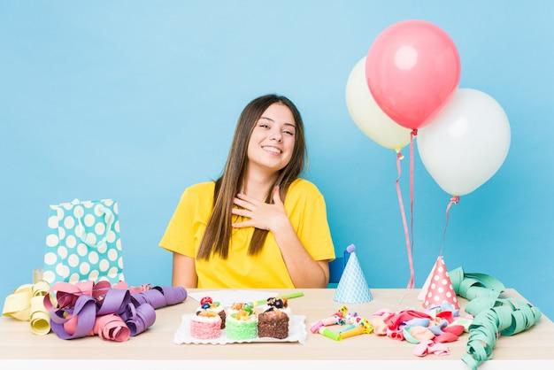 誕生日を整理する若い白人女性は大声で胸に手を当てて笑います。
