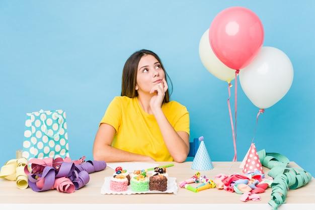 疑わしいと懐疑的な表情で横向きの誕生日を整理する若い白人女性。