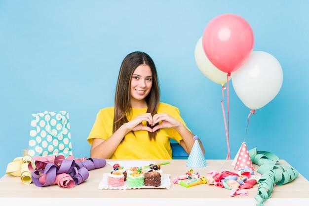 Молодая кавказская женщина организует день рождения, улыбаясь и показывая руками форму сердца.