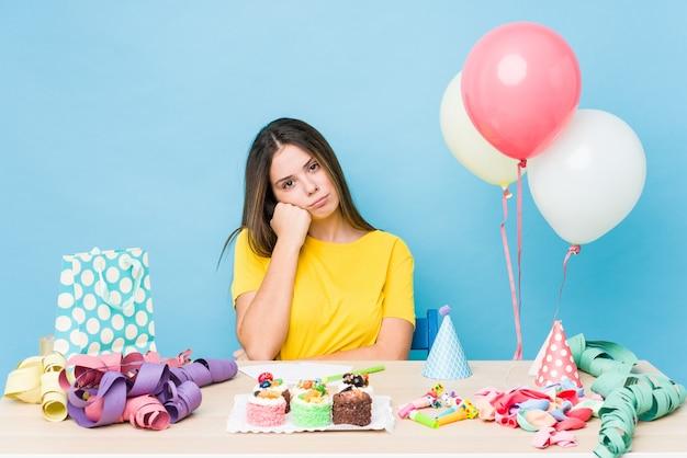 Молодая кавказская женщина, организующая день рождения, чувствует себя грустной и задумчивой, глядя на пространство для копирования.