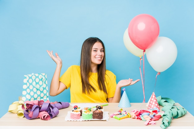 Young caucasian woman organizing a birthday doubting and shrugging shoulders in questioning gesture.