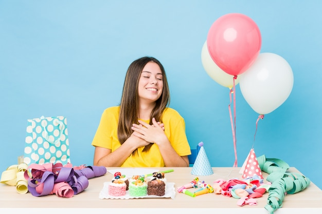 Young caucasian woman organizing a birthday laughing keeping hands on heart