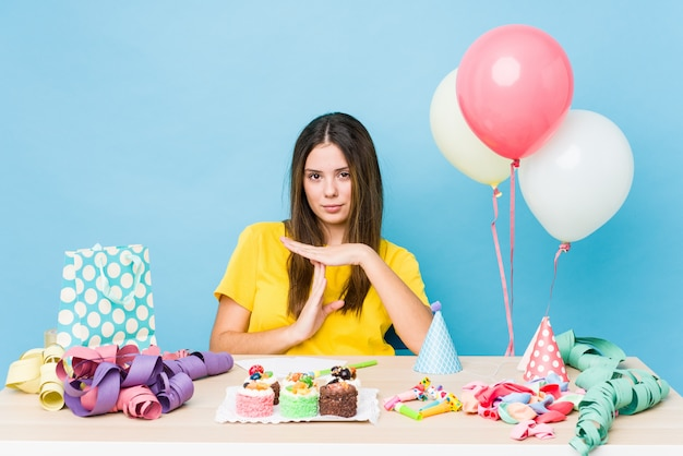 Young caucasian woman organizing a birthday showing a timeout gesture.