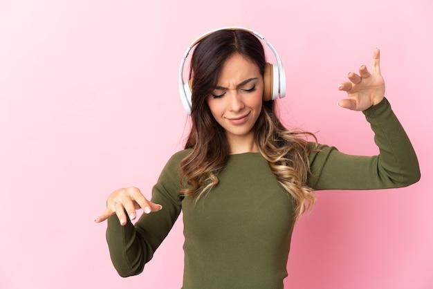 Молодая кавказская женщина на изолированном фоне, слушает музыку и танцует