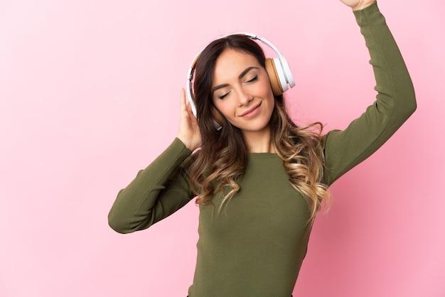 Молодая кавказская женщина над изолированной стеной слушает музыку и танцует