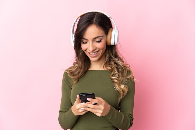 Молодая кавказская женщина над изолированной стеной слушает музыку и смотрит на мобильный