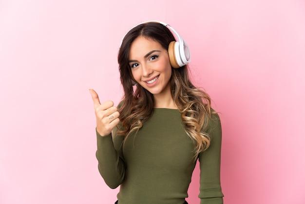 孤立した壁の上の若い白人女性が音楽を聴いて、親指を立てて