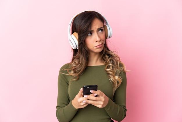 Молодая кавказская женщина над изолированной стеной слушает музыку с помощью мобильного телефона и думает