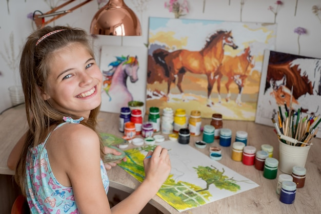 Young caucasian woman painter working in canvas in art studio