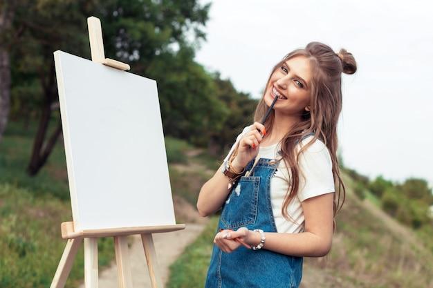 若い白人女性の外のキャンバスに絵
