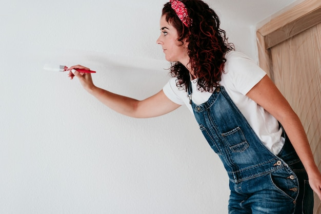 Young caucasian woman painting the room walls with white color. do it yourself and new home concept