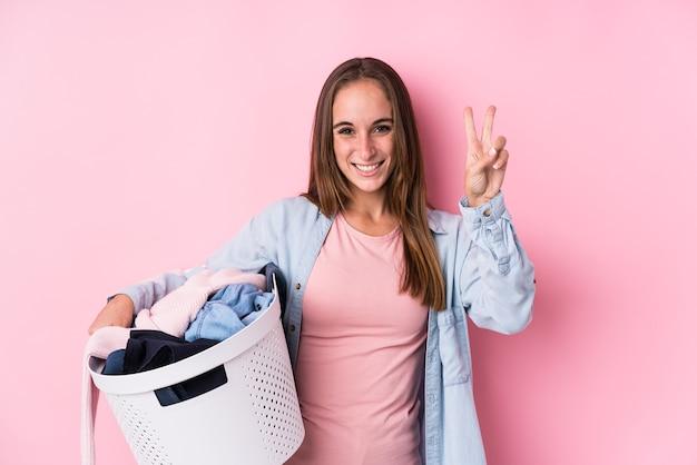 Молодая кавказская женщина, поднимающая грязную одежду, изолировала, показывая номер два пальцами.