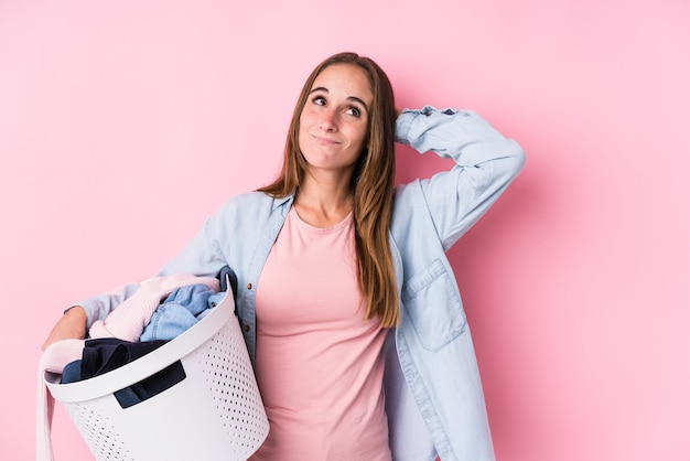 Young caucasian woman picking up dirty clothes isolated touching back of head, thinking and making a choice.