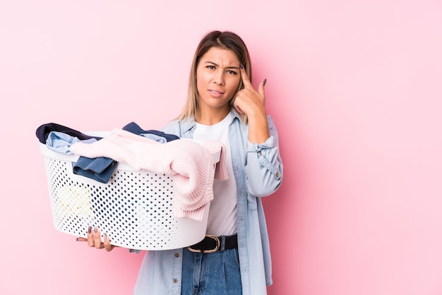 Young caucasian woman picking up a dirty clothes showing a disappointment gesture with forefinger.