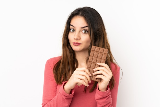 Young caucasian woman on pink wall taking a chocolate tablet and having doubts