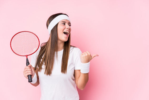 Young caucasian woman playing badminton points with thumb finger away