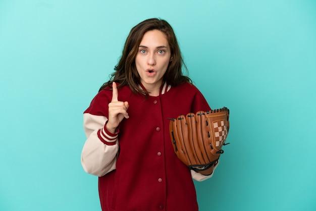 Молодая кавказская женщина играет в бейсбол, изолированную на синем фоне, намереваясь реализовать решение, подняв палец вверх