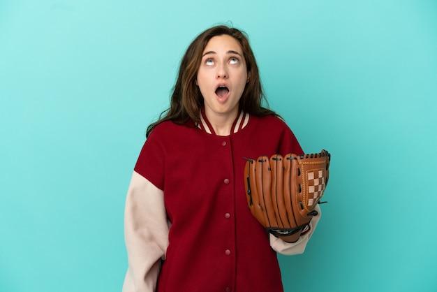 Молодая кавказская женщина играет в бейсбол на синем фоне, глядя вверх и с удивленным выражением лица