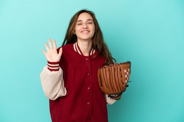 Молодая кавказская женщина играет в бейсбол на синем фоне, салютуя рукой с счастливым выражением лица