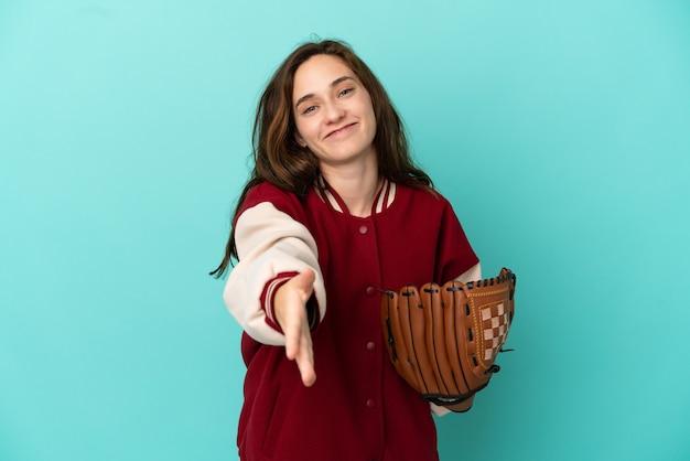 파란 배경에 격리된 야구를 하는 젊은 백인 여성이 좋은 거래를 성사시키기 위해 악수를 하고 있다