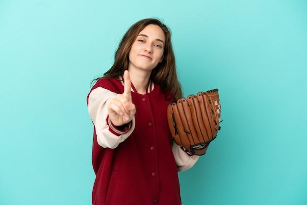 파란색 배경에 격리된 야구공을 하고 있는 백인 젊은 여성이 손가락을 들고 들어올리는 모습